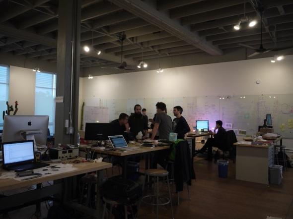 スタートアップの起業家たちは、大きな部屋で机を並べて仕事をする